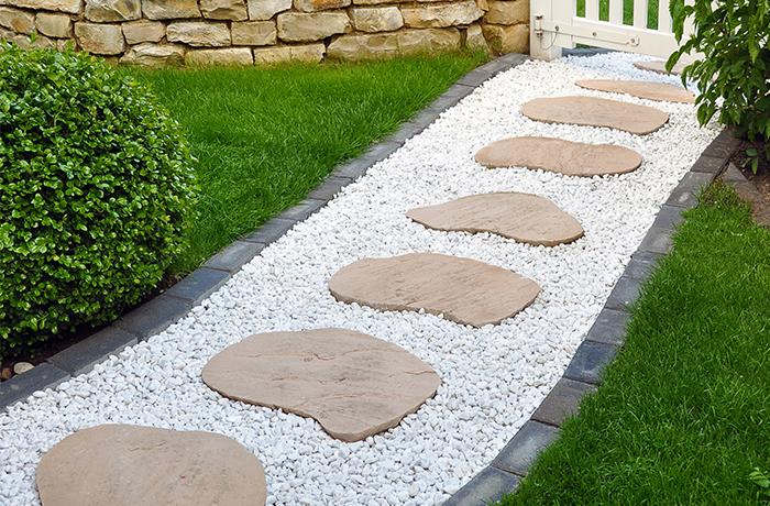 Aufwendiger Gartenweg aus weißem Kies mit kontrastvollen Trittplatten