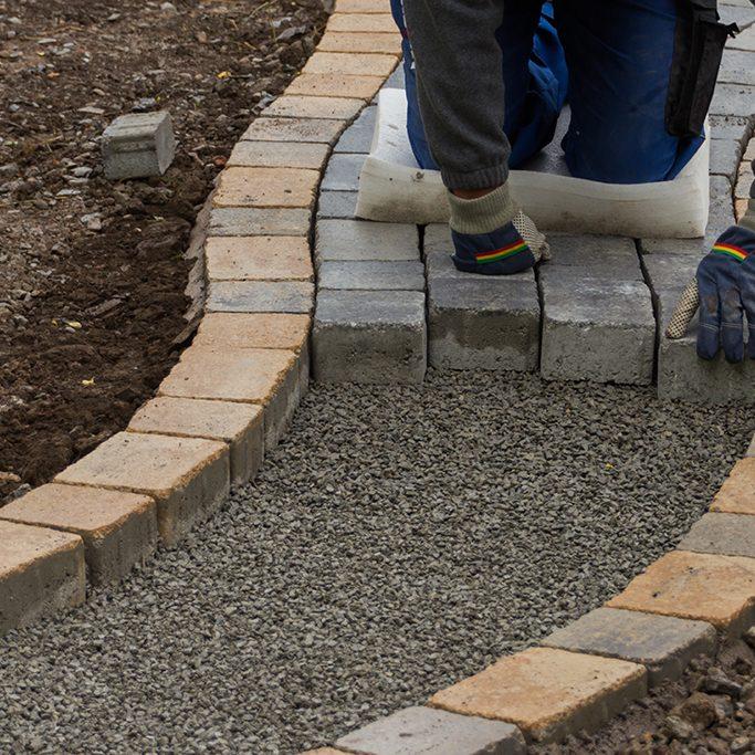 Verlegearbeiten, geschwungener Gartenweg aus Pflastersteinen